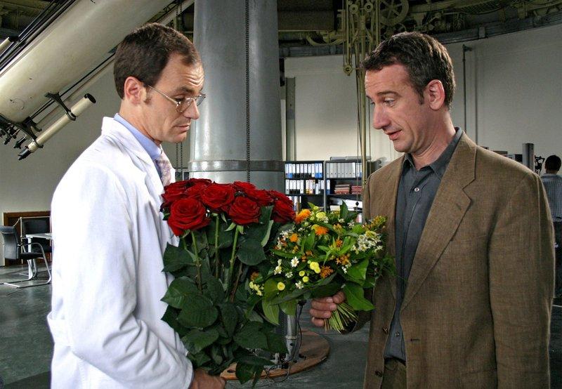 Dr. Peter Grainernapp (Heio von Stetten, rechts) und sein Kollege Dr. Neumann (Anian Zollner) wollen beide einer verehrten Mitarbeiterin zum Geburtstag gratulieren. – Bild: ARD Degeto/ARD Degeto/Sandor Domonkos