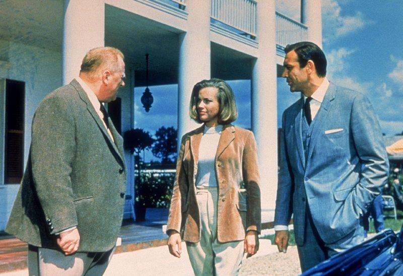 Goldfinger (Gert Fröbe, l.) ist es mit Hilfe der Pilotin Pussy (Honor Blackman) gelungen, James Bond (Sean Connery) gefangen zu nehmen. – Bild: TVNOW / © 1964 Danjaq