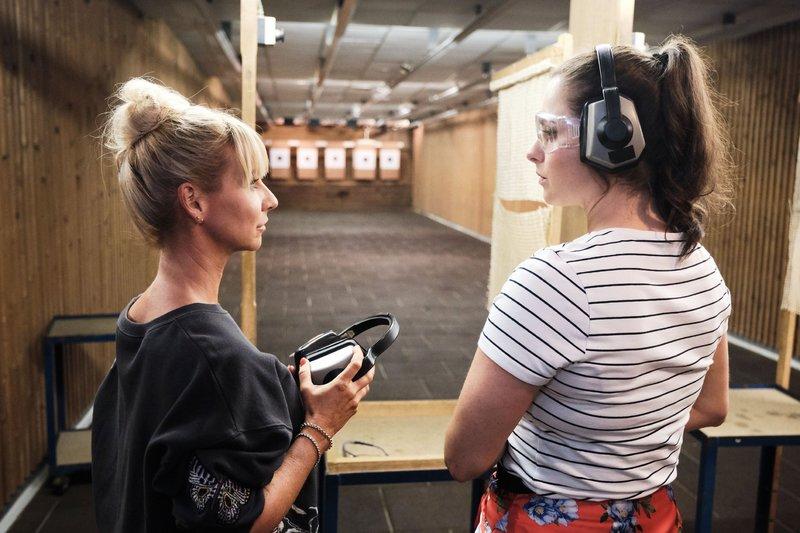 Saskia (Antonia Michalsky, r.) ist mit Ute (Isabell Hertel) auf dem Schießstand und erkennt unwohl, dass sich die Realität deutlich vom Videospiel unterscheidet. – Bild: TVNOW / Stefan Behrens