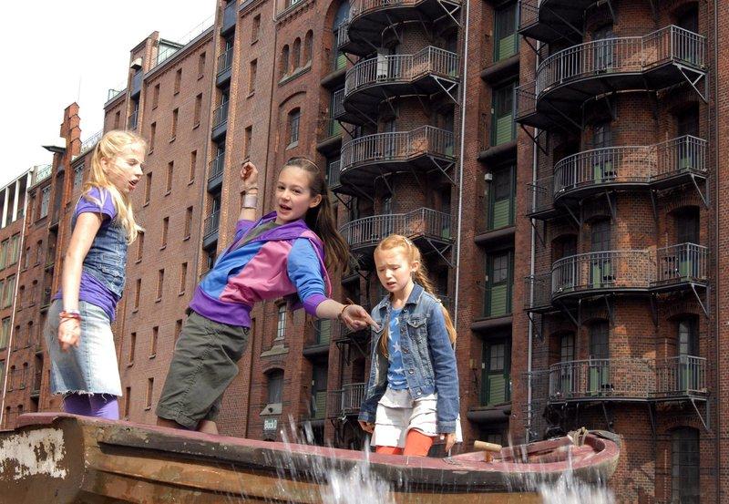 Lina (Lale H. Mann, Mitte) fällt in der Speicherstadt ins Wasser. Sophie (Katherina Unger, li.) und Emma (Aurelia Stern, re.) haben Angst um sie.– Bild: NDR/Romano Ruhnau