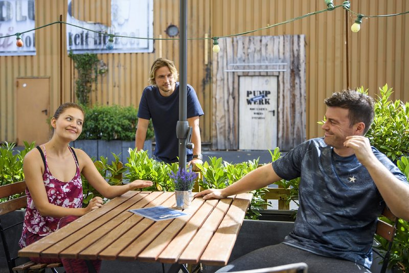 Nathalie (Amrei Haardt) sitzt mit Ben (Jörg Rohde, r.) im Biergarten und entscheidet spontan, Finn (Christopher Kohn) die Wahrheit zu sagen. – Bild: TVNOW / Julia Feldhagen