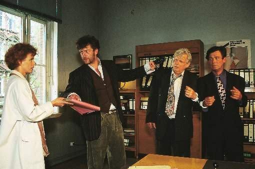 Während Berger (Dominic Raacke, 2.v.li.) seine Geisel Severin (Christian Doermer, 2.v.re.) und Anwalt Manthey (Matthias Fuchs) mit der Pistole bedroht, zwingt er Kommissarin Eva (Sylvia Haider) seine Akte zu besorgen – Bild: RTLplus / Boris Laewen