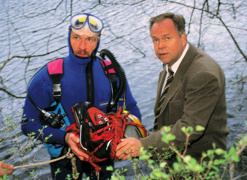 Die Polizei hat einen toten Jungen im Wasser gefunden. Kriminalhauptkommissar Stefan Kehler (Wolfgang Bathke, re.) spricht mit einem Taucher (Komparse) über die Beweissicherung. – Bild: RTLplus