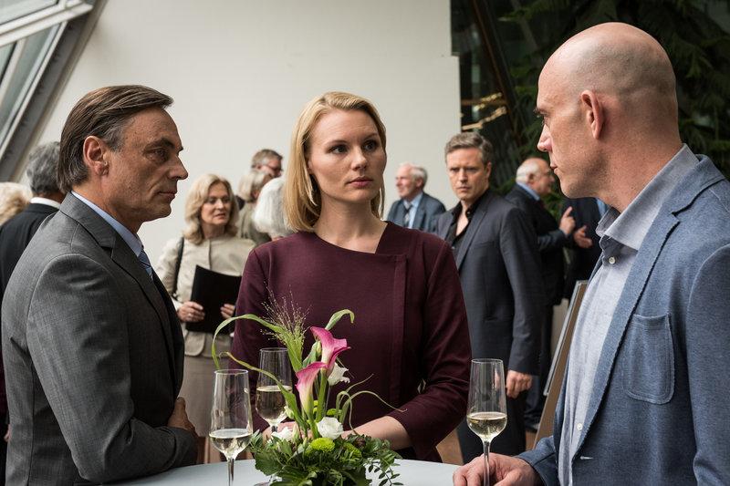 Otto Falk (Peter Benedict, l.) hört, wie Eva Blumenthal (Rosalie Thomass, M.) Frank Rolfskind (Robert Dölle, r.) beschuldigt, am Tod von Bertram Kaiser beteiligt zu sein. – Bild: ZDF und Christoph Assmann