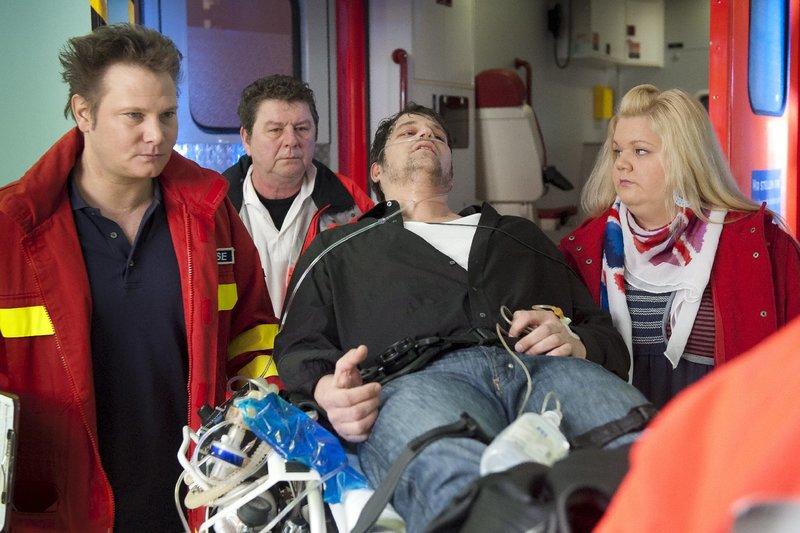 Frauke (Manuela Wisbeck) begleitet ihr Date ins Krankenhaus. Der Fremde (Georg Jungmann, liegend) wurde von einer Schlange gebissen. Philipp (Fabian Harloff, l.) und ein Kollege (Komparse) versorgen ihn. – Bild: ZDF und Boris Laewen-bola