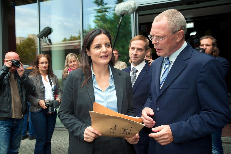 Dr. Susanne Mertens (Elisabeth Lanz, links) konfrontiert OB Herrenbrück (Frank Siekel, rechts) mit einer Unterschrift als Beweis, dass sie Opfer einer Intrige von Dr. Bernd Schröder (Nils Bruno Schmidt, Mitte) wurde. – Bild: Bernd Cramer
