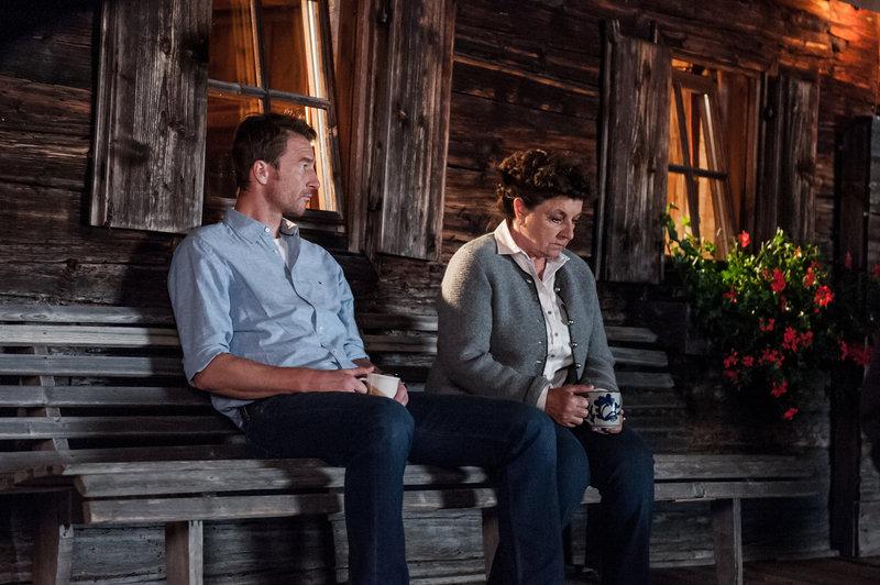 """Der Bergdoktor - Fremdes Herz"""": Hans (Heiko Ruprecht) und Lisbeth Gruber (Monika Baumgartner) sitzen vor dem Haus auf einer Holzbank. Beide halten eine Tasse in der Hand. – Bild: ZDF"""