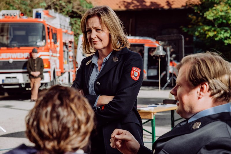 Veronika Brunner (Senta Auth) in ihrer Feuerwehr-Uniform. Rechts im Bild: Max Brunner (Michael Grimm). – Bild: BR/Nadya Jakobs