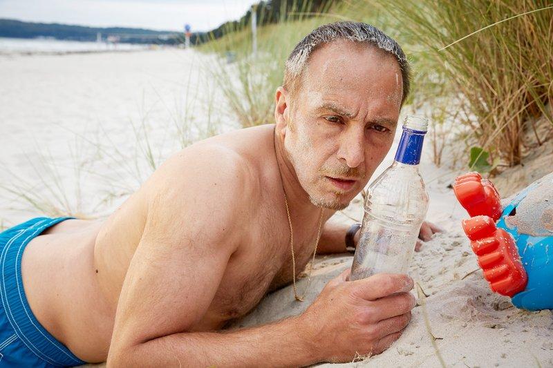 Semir (Erdogan Atalay) wird - völlig verkatert - am Strand wach. – Bild: RTL / Guido Engels