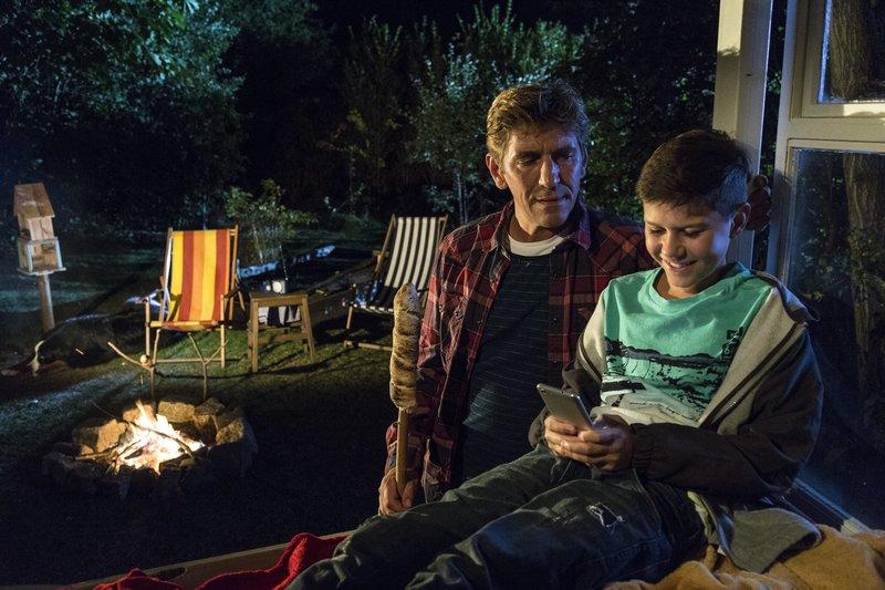 Selbst mit einem schönen Lagerfeuer kann Fritz Fuchs (Guido Hammesfahr, l.) Mattis (Noah Calvin, r.) nicht vom Smartphone weglocken. – Bild: ZDF und Antje Dittmann.