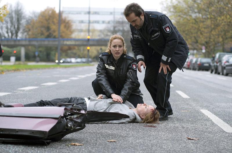 Kristin Marquard (Monika Blumtritt, M.) wird bei einem Autounfall schwer verletzt. Paul Dänning (Jens Münchow, r.) und Nina Sieveking (Wanda Perdelwitz, l.) bei Wiederbelebungsmaßnahmen. – Bild: ARD/Thorsten Jander