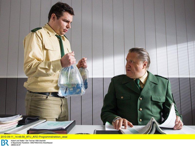 Riedl (Paul Sedlmeir, links) hat zwei neue Fische für das Aquarium von Staller gekauft. Allerdings konnte er keinen grünen Fisch auftreiben. Es gab nur einen gelben oder einen blauen Fisch. Polizeirat Girwidz (Michael Brandner) ist enttäuscht. – Bild: ARD/ARD/TMG/Chris Hirschhäuser