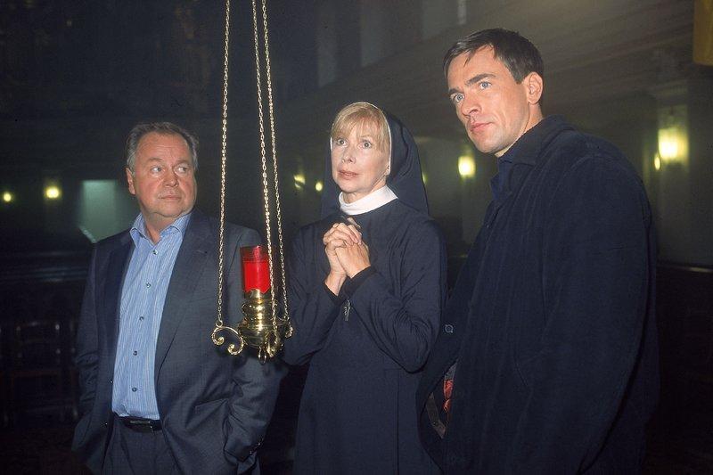 Auch die Haushälterin des ermordeten Pfarrers, Schwester Agnes (Ursela Monn) gehört zu den Verdächtigen. Die Beamten (li. Wolfgang Bathke, re. Wolfgang Krewe) befragen sie zu der Lebensweise des Mordopfers. – Bild: RTLplus
