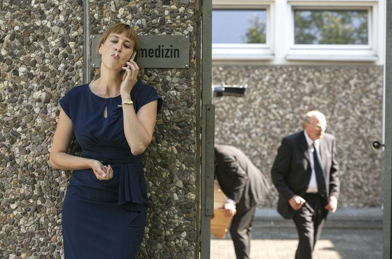 Dr. Schmidt (Helene Grass, l.) nutzt ein Telefonat mit dem Professor für eine kurze Pause (mit Komparsen, r.). – Bild: ARD/Kai Schulz