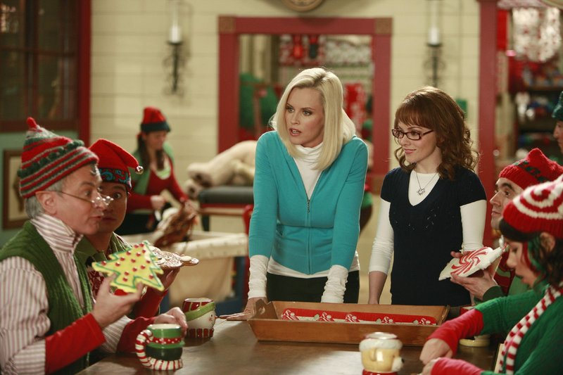 Mary (Jenny McCarthy, M.) erkennt, dass Teri (Kelly Stables, 3.v.r.) sich in ihrer Abwesenheit offenbar nicht nur um die Arbeit der Elfen Gary (Richard Side, l.), Dave (James Higuchi, 2.v.l.) Skip (Gabe Khouth, 2.v.r.) und Lucy (Jessica Parker Kennedy) gekümmert hat... – Bild: SUPER RTL