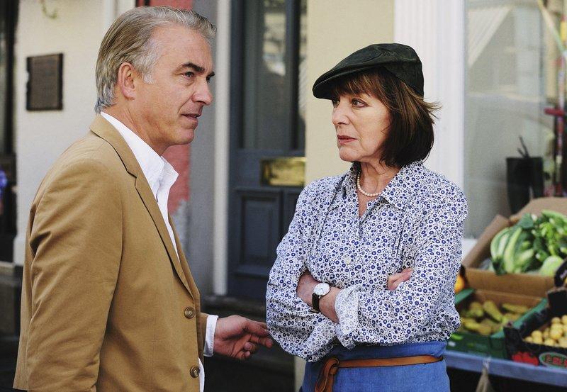 """Michael Lloyd Glynn (Christoph M. Ohrt) erkundigt sich bei Margret Pollard (Heidelinde Weis) nach Alex. – Bild: """"ARD Degeto/ARD Degeto/Warren Orchard"""" (S2)"""