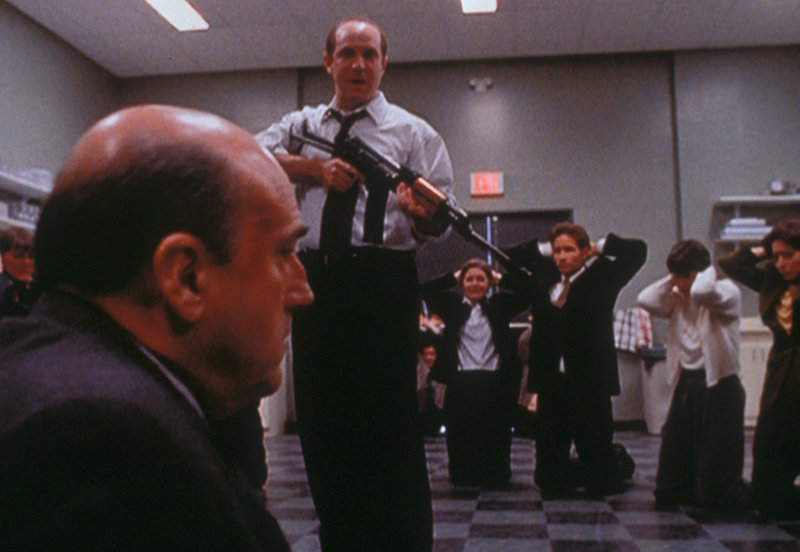 Gary Lambert (Brian Markinson, M.) hat einige seiner Kollegen und Mulder (David Duchovny, 3.v.r.) als Geiseln genommen, um seinen Chef Greg Pinkus (John Apicella, l.) als Monster zu entlarven. – Bild: TM + © 2000 Twentieth Century Fox Film Corporation. All Rights Reserved. Lizenzbild frei