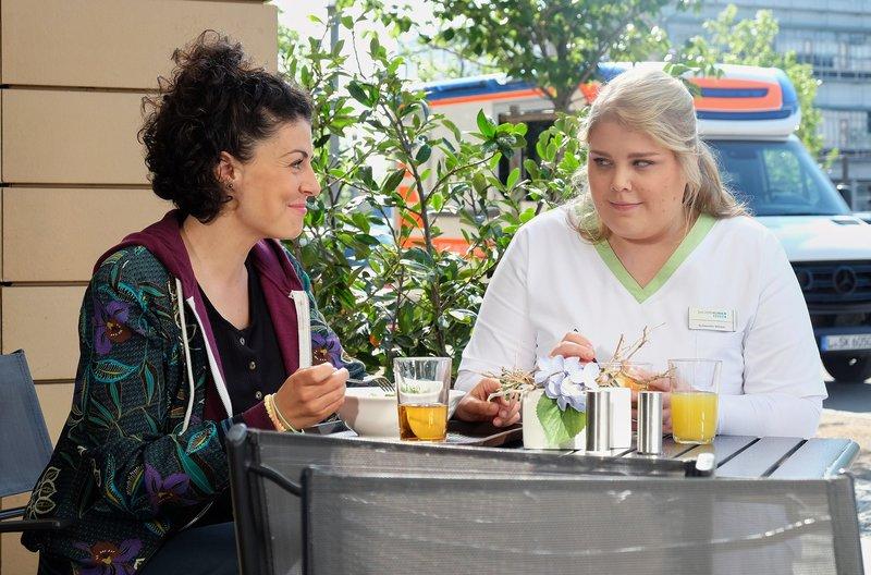 Schwester Miriam (Christina Petersen, rechts) verbringt mit Rieke Machold (Liza Tzschirner), der Enkelin einer Patientin, ihre Mittagspause. Die beiden verstehen sich auf Anhieb. Miriam ist leicht verunsichert, denn plötzlich liegt eine regelrecht flirtive Spannung in der Luft. – Bild: BR/MDR/Saxonia Media/Sebastian Kiss