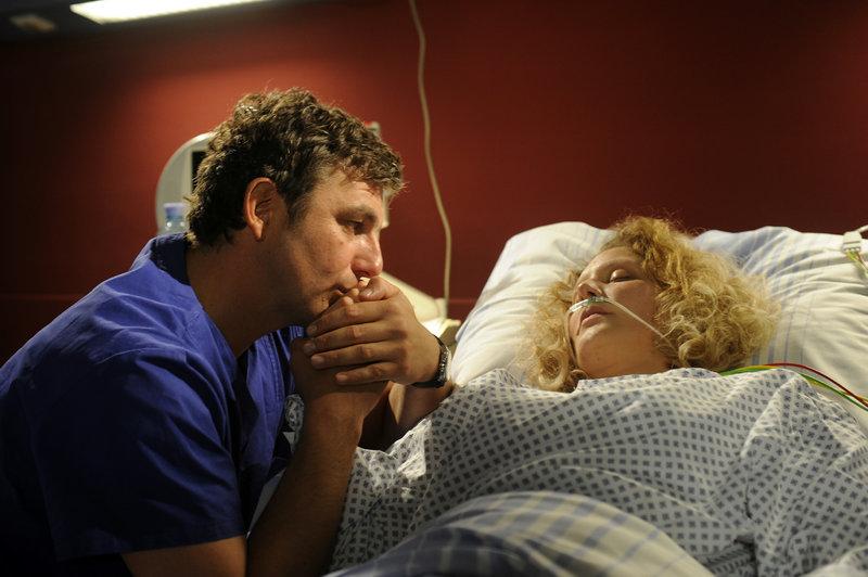 Andrea (Tessa Mittelstaedt, r.) liegt geschwächt im Krankenbett. Martin (Hans Sigl, l.) ist bei ihr, hält ihre Hand. – Bild: ZDF und Thomas R. Schumann