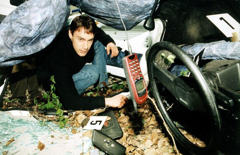 Kommissar Brandtner (Gedeon Burkhard) nimmt das Autowrack etwas genauer unter die Lupe. Er entdeckt ein Mobiltelefon. Hat die Verunglückte kurz vor ihrem Unfall ein Gespräch geführt? – Bild: Sat.1 Gold