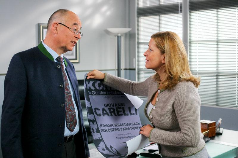 Die Auswahl eines Plakats sorgt bei Polizeichef Achtziger (Alexander Duda, l.) und Marie (Karin Thaler, r.) für Aufregung. – Bild: ZDF und Christian A. Rieger - klick