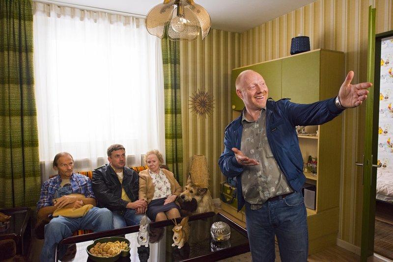 Die neue Traum-WG: Rudi Birkenberger (Simon Schwarz) präsentiert Franz Eberhofer (Sebastian Bezzel, Mitte), Vater Eberhofer (Eisi Gulp, links) und Oma Eberhofer (Enzi Fuchs, rechts) seine Münchner Wohnung. – Bild: BR/Constantin Film/Bernd Schuller