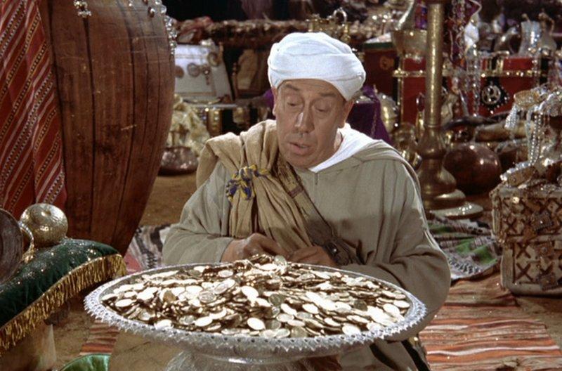 Ali Baba (Fernandel) nimmt sich aus der Räuberhöhle so viel Gold mit, wie er tragen kann. – Bild: MDR/Studiocanal