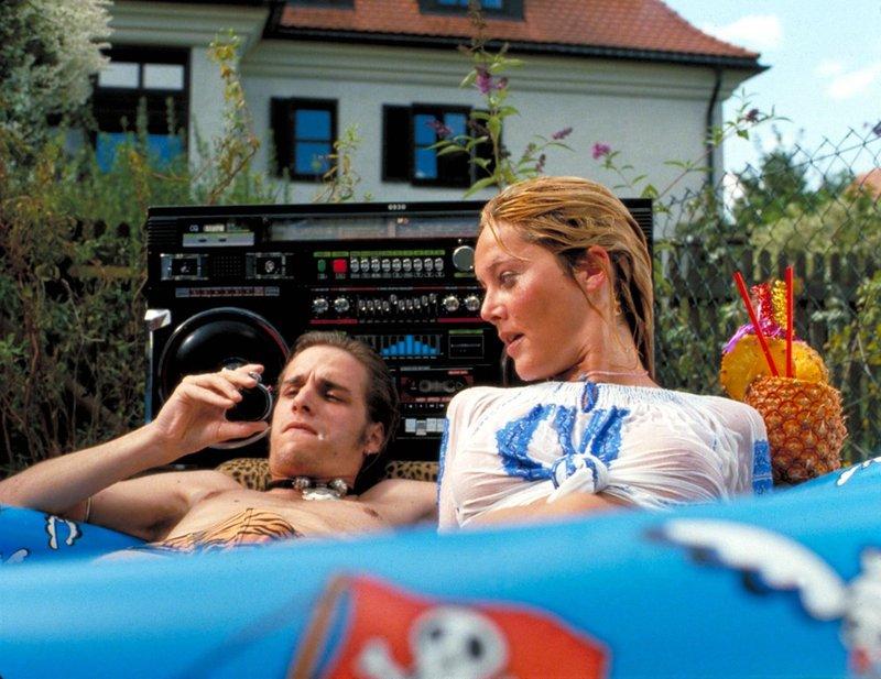Meister Eder liegt mit seiner Freundin (Max von Thun und Doreen Dietel) im Planschbecken. – Bild: BR/Zephir Film GmbH