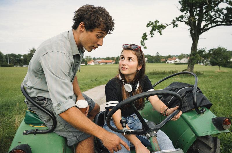 Leonie (Alina Abgarjan) lässt sich von Laurenz (Klaus Steinbacher) zeigen, wie man Traktor fährt – Bild: ARD Degeto/Hendrik Heiden