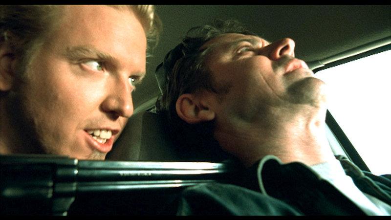 Der Anhalter (Jake Busey) bedroht Jim (C. Thomas Howell) mit einer Waffe... – Bild: RTL II