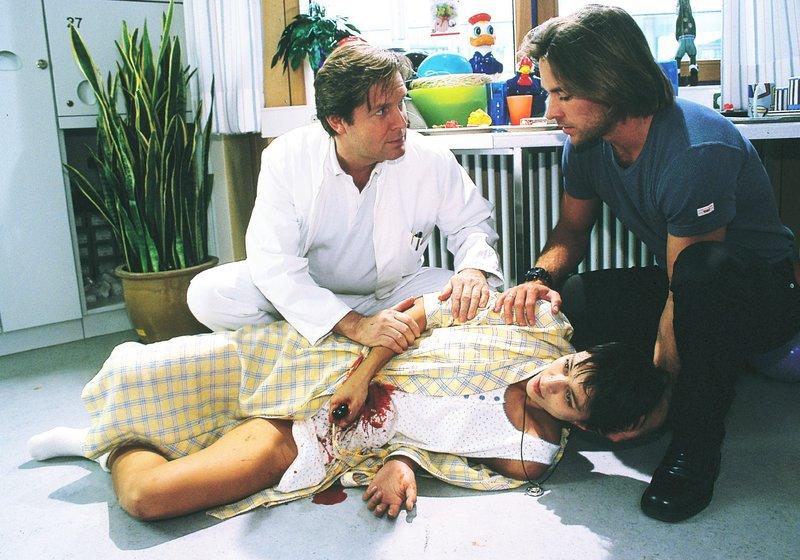 Dr. Stefan Frank (Sigmar Solbach, li.) und Nick (Marco Girnth) finden im Krankenzimmer die schwer verletzte Simone (Yvonne de Bark) vor. – Bild: RTLplus