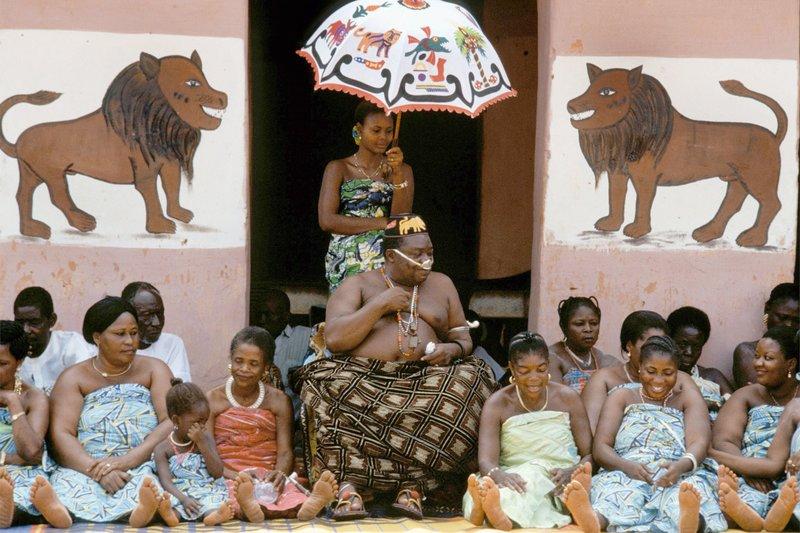 Der jetzige König Dédjalagni Agoli-Agbo XII. auf dem Thron derer von Abomey, mit Hofstaat samt Ehefrauen. Ein Filter aus Silber bewahrt ihn davor, dieselbe Luft atmen zu müssen wie das gewöhnliche Volk. – Bild: SWR/SWR