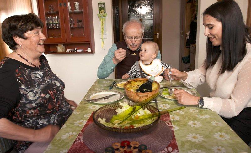 Oma Paula erklärt Enkelin Theresa das Rezept, Opa Theo kümmert sich um Theresas Sohn Hector. – Bild: SWR