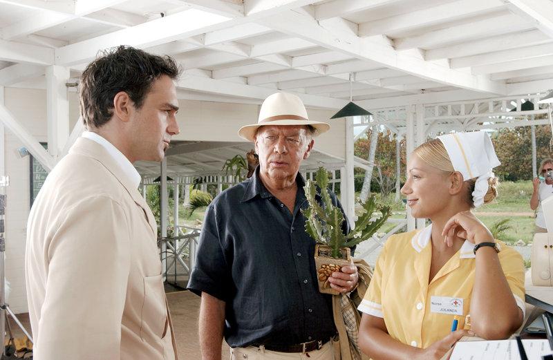 """""""Klinik unter Palmen"""", """"Gefährliches Spiel."""" Dr. Hofmann übernimmt die Leitung der Klinik 'Santa Lucia' auf Kuba. Kein leichter Job, denn das neu besetzte Team muss erst zusammenwachsen. Ein """"Sorgenkind"""" ist der Chirurg Dr. Ritter, der im Ruf steht, ein Frauenheld zu sein. Er lässt sich auf eine Affäre mit der Frau des Polizeichefs ein. Der eifersüchtige Ehemann schöpft bald Verdacht. Nach einem anstrengenden Arbeitstag will sich Hofmann bei seiner neuen Liebe, der Fotografin Dorothea, erholen. Doch der Abend endet nicht wie geplant.Im Bild (v.li.): Harry Blank (Enrique Gomez), Klausjürgen Wussow (Frank Hofmann), Radost Bokel (Jolanda). – Bild: SRF 1"""