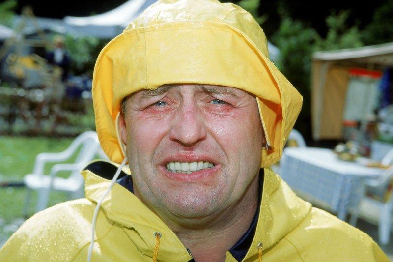 Benno (Willi Thomczyk) hat Heuschnupfen. Um den lästigen Pollen zu entgehen, setzt er sich mit einem Regenanzug unter den Rasensprenger. – Bild: RTLplus