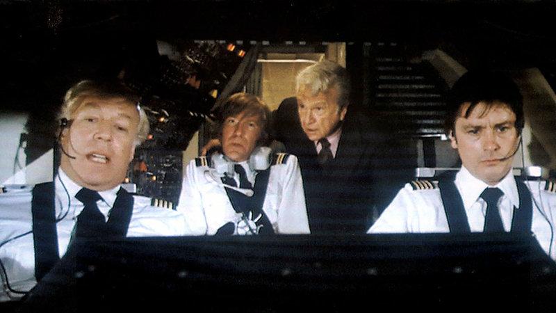 Eli Sanders (Eddie Albert, 2.v.re.) erkundigt sich bei den Piloten Merand (Alain Delon, re.) , Patroni (George Kennedy, li.) und Peter O'Neill (David Warner) nach dem Schaden an der Concorde... – Bild: RTL Zwei
