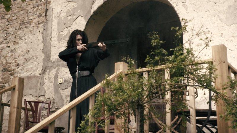 Anna (Claudia Mehnert) steht mit einem Gewehr auf der Veranda des Landhauses und zielt. – Bild: ZDF und Felix Cramer