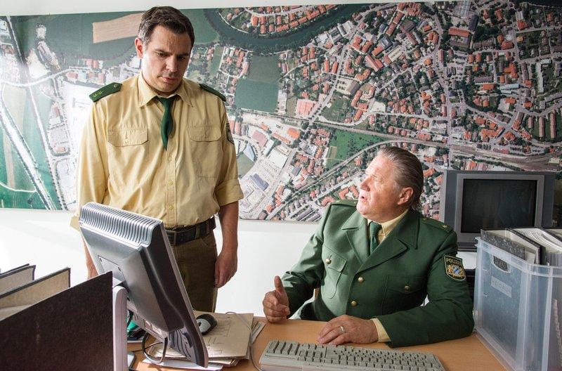 Riedl (Paul Sedlmeir, links) hilft Girwidz (Michael Brandner), sich vorübergehend im Konferenzraum einzurichten. – Bild: ARD/BR/TMG/Marco Meenen
