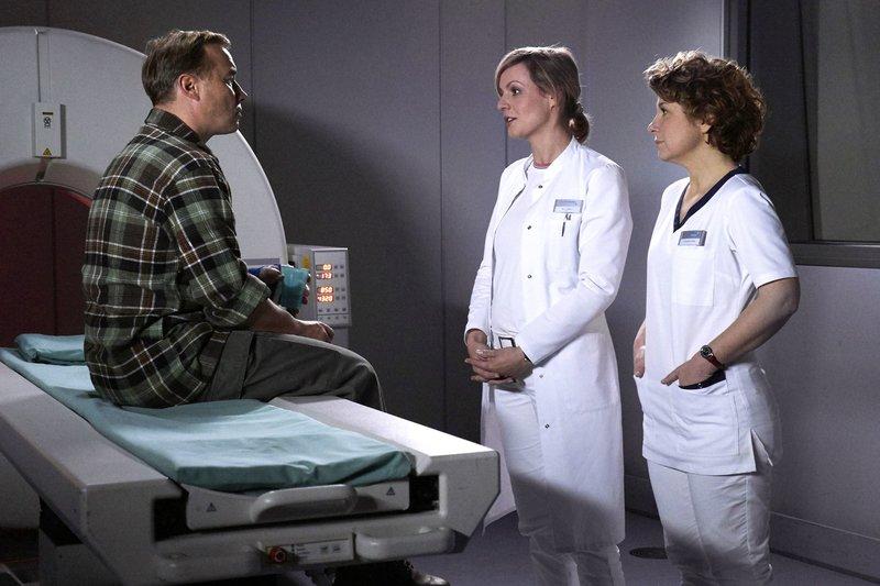 Der Forstwirt Mark Wiese (Thomas Arnold, li.) ist gestürzt und nun muss zur Kontrolle ein CT der Halswirbelsäule gemacht werden. Doch Mark ist Klaustrophobiker und es ist für ihn schlichtweg unmöglich, sich still ins CT zu legen. Schwester Ulrike (Anita Vulesica, re.) ahnt, was das für Mark Wieses Alltag bedeutet. Doch das CT muss gemacht werden. Dr. Lea Peters (Anja Nejarri, mi.) gibt ihm ein Beruhigungsmittel und Schwester Ulrike die beruhigenden Worte dazu. – Bild: MDR/Wernicke