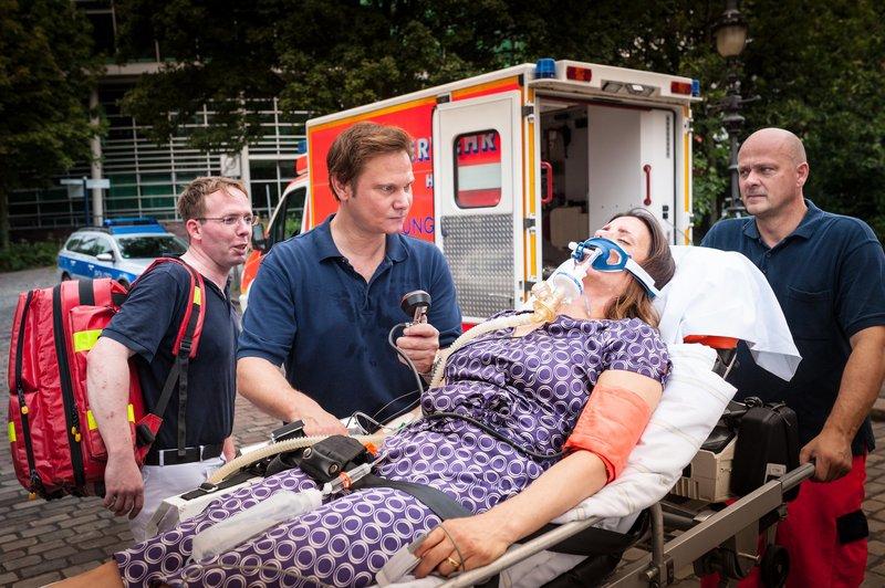Dr. Haase (Fabian Harloff, 2.v.l.) macht sich Sorgen. Er hat bei seiner Patientin (Elisabeth Baulitz) eine schwere allergische Schockreaktion diagnostiziert, doch ist noch unklar, worauf sie so stark reagiert hat. – Bild: ZDF und Boris Laewen./Boris Laewen