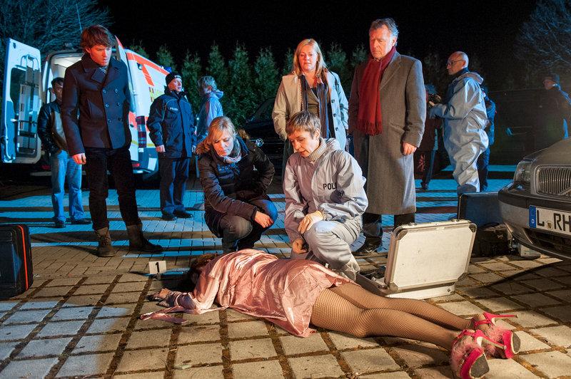 Als Hajo (Andreas Schmidt-Schaller, 2.v.r.), Ina (Melanie Marschke, 2.v.l.) und Tom (Steffen Schroeder, l.) zum Tatort kommen, ist Dagmar Schnee (Petra Kleinert, 3.v.r. stehend), die Kollegin der Sitte bereits vor Ort. Wer ist für den neuen Fall zuständig? Prof. Rossi (Anna Stieblich, 3.v.r. sitzend) kann auf jeden Fall bestätigen, dass es sich um einen Mord handelt. – Bild: ZDF und Uwe Frauendorf