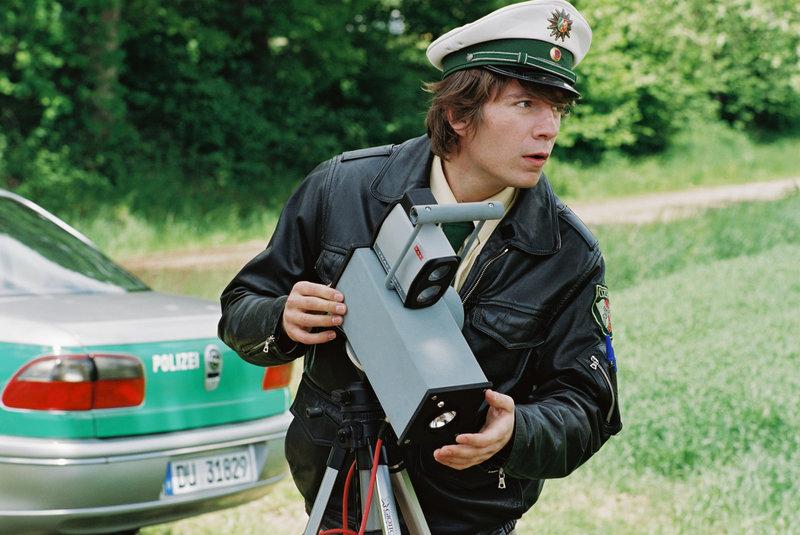 Karl-Heinz (Luke J. Wilkins) muss auf Befehl seines Bosses an einer Radarfalle Strafdienst schieben. – Bild: CONSTANTIN