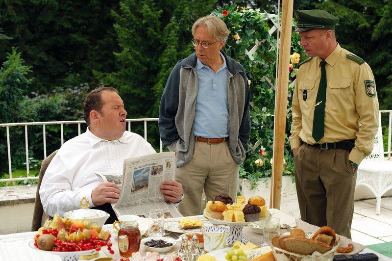 Benno (Ottfried Fischer, l.) sitzt mit Rambold (Gerd Anthoff, M.) beim Frühstück, als Schmidt (Norbert Mahler, r.) ihm die alte Zeitung vorbeibringt, die seine Theorie bestätigt ... – Bild: BR/Sat.1/Walter Wehner