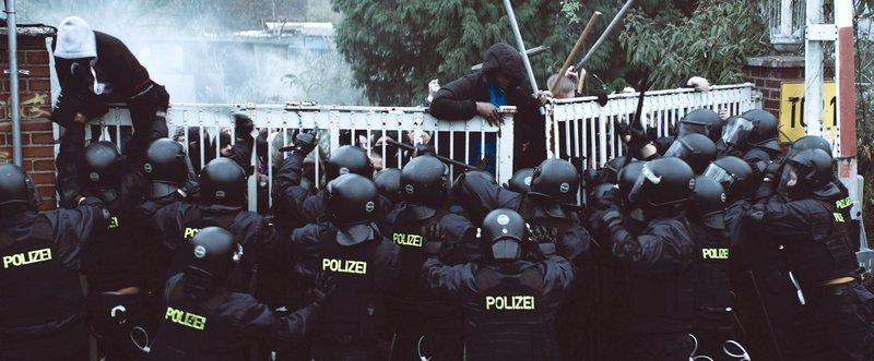 Nachdem einer der Flüchtlinge getötet wurde, versuchen andere aus der Transitzone auszubrechen, gehindert von einem massiven Polizeieinsatz. – Bild: SWR/augenschein Filmproduktion