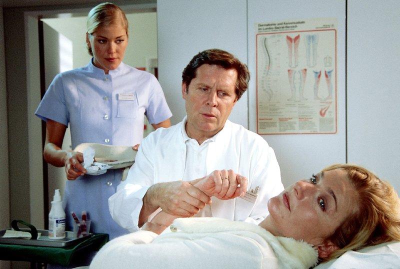 Dr. Stefan Frank (Sigmar Solbach) muss seiner Patientin Verena (Saskia Vester, liegend) mitteilen, dass sie Brustkrebs hat. Laura (Cecilia Kunz) verfolgt die beklemmende Situation. – Bild: RTLplus / Elke Werner