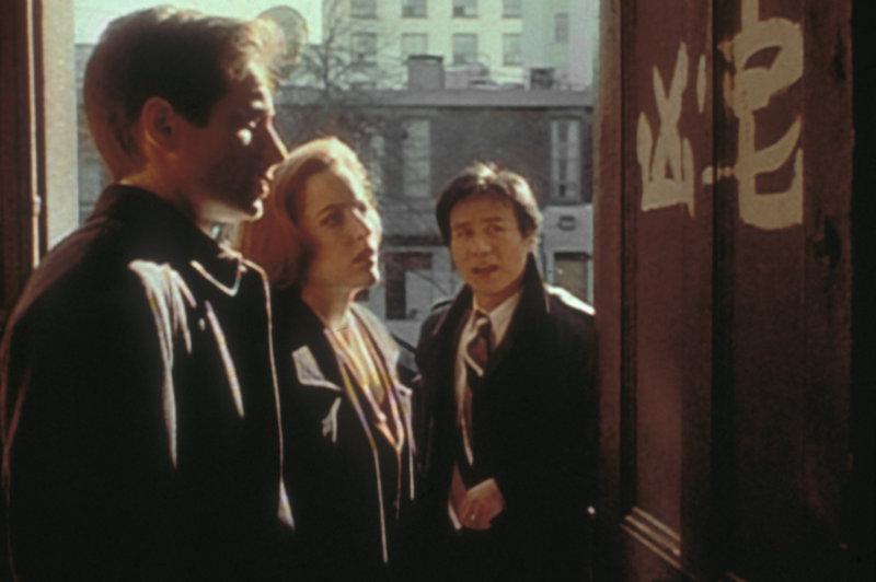 Obwohl Detective Glen Chao (B.D. Wong, r.) chinesischer Abstammung ist, kann er die Schriftzeichen an der Wohnungstür eines Mordopfers für Mulder (David Duchovny, l.) und Scully (Gillian Anderson, M.) nicht übersetzen. – Bild: TM + © 2000 Twentieth Century Fox Film Corporation. All Rights Reserved. Lizenzbild frei