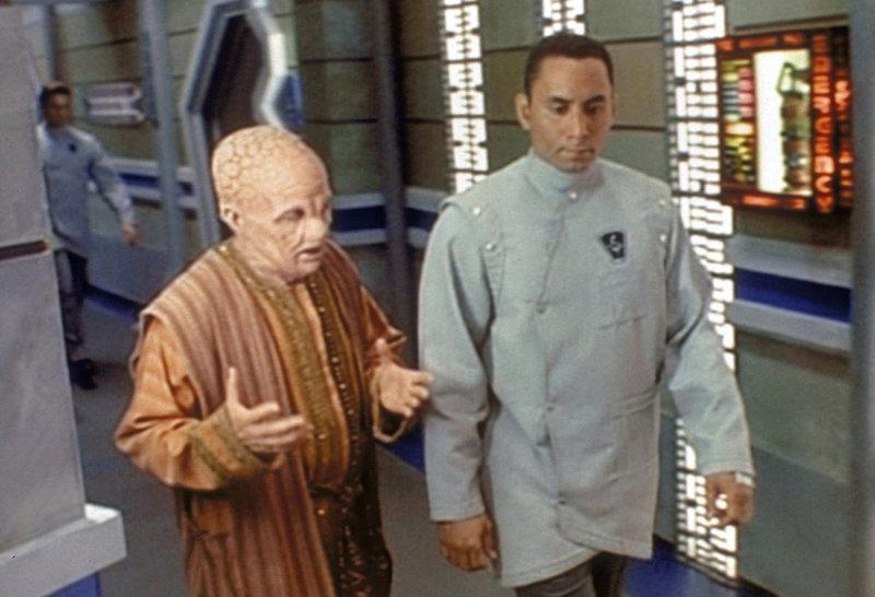 Dr. Franklin (Richard Biggs, r.), der Chefarzt auf Babylon 5, im Gespräch mit seinem Markab-Kollegen Lazarenn (Jim Norton, l.), der ihm erklärt, dass die Seuche schon einmal aufgetreten ist und dass die Markab glauben, nur jemand, der unmoralisch lebt, könne von dieser Seuche befallen werden. – Bild: ProSieben MAXX