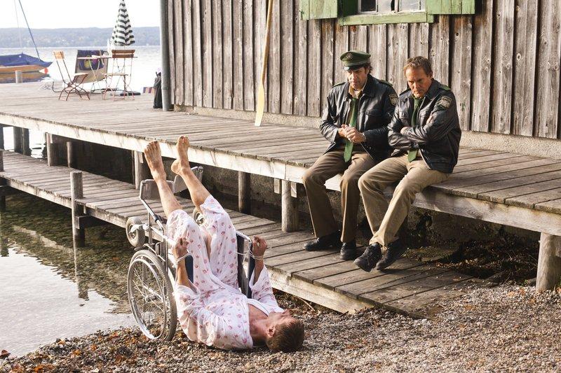 Hubert (Christian Tramitz, rechts) und Staller (Helmfried von Lüttichau, Mitte) entdecken eine Leiche im See, die an einen Rollstuhl gefesselt ist. Schnell wird klar, dass es sich hier nicht um einen tragischen Unfalltod handelt. Der Tote ist Fabian Pfeifer (Komparse), der zu Lebzeiten keineswegs auf einen Rollstuhl angewiesen war. – Bild: TMG / Chris Hirschhäuser