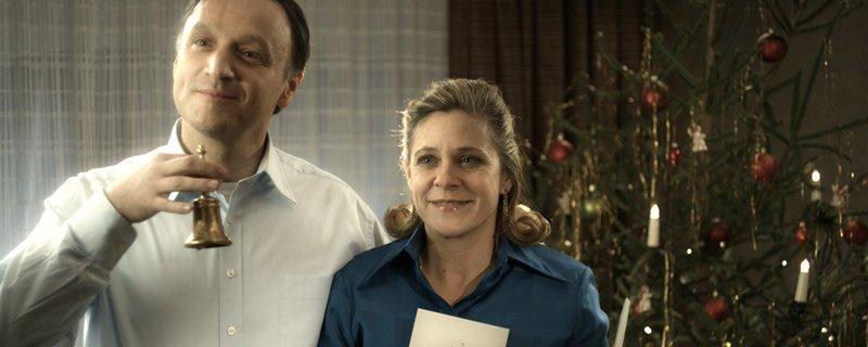 Vater Bernhard (Frank Voß) und Mutter Brigitte (Tina Eschmann) läuten zur Bescherung. – Bild: NDR