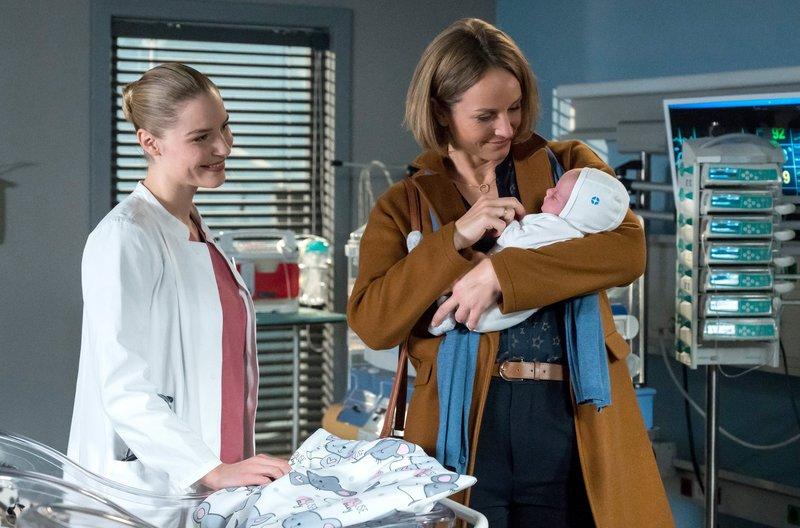 Julia Berger (Mirka Pigulla, l.) zeigt der frisch gebackenen Oma ihr Enkelkind. Nina Sander (Lara Joy Körner, r.) ist überwältigt. – Bild: ARD/Jens Ulrich Koch